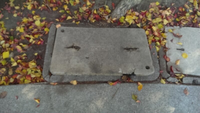 Image of recessed in ground broken utility box. Risk of pedestrian injury